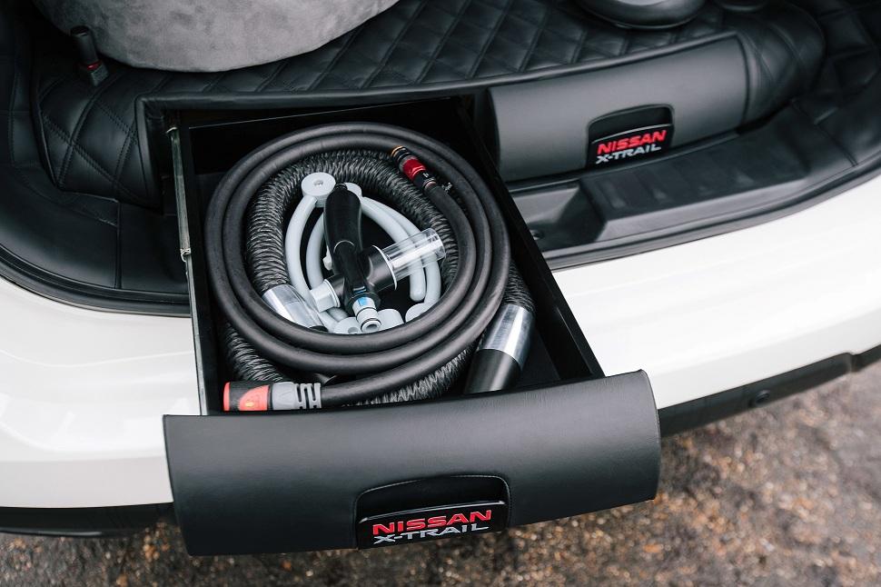 Les systèmes d'attache de la douche et du séchoir sont rangés dans un tiroir coulissant situé sur le rebord du coffre. De nouveaux compartiments latéraux ont été ajoutés afin de ne pas encombrer l'espace. Le concept Nissan X-TRAIL 4Dogs possède naturellement une grille de séparation située au-dessus des sièges arrière – accessoire d'origine signé Nissan et disponible à l'achat.